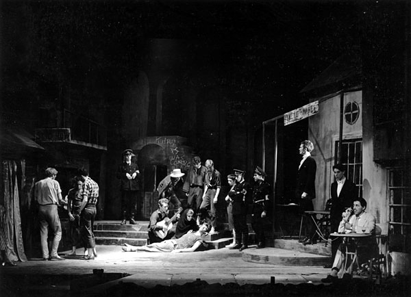 Garry O'Connor plays the guitar, Ian McKellen dies, tall Simon Relph watches and Richard Cottrell, sitting, plays out front in ''Camino Real'', ADC 1958