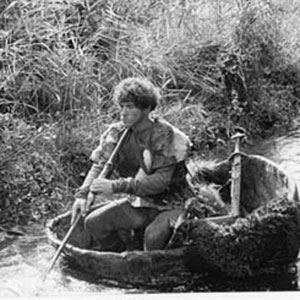 Roger the Bandit (Ian McKellen) paddling his kayak in an Irish backwater.