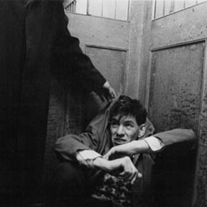 Walter (Ian McKellen) cowers in fear of  bullies in the factory elevator.